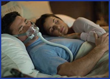 Photo of man using CPAP machine with woman